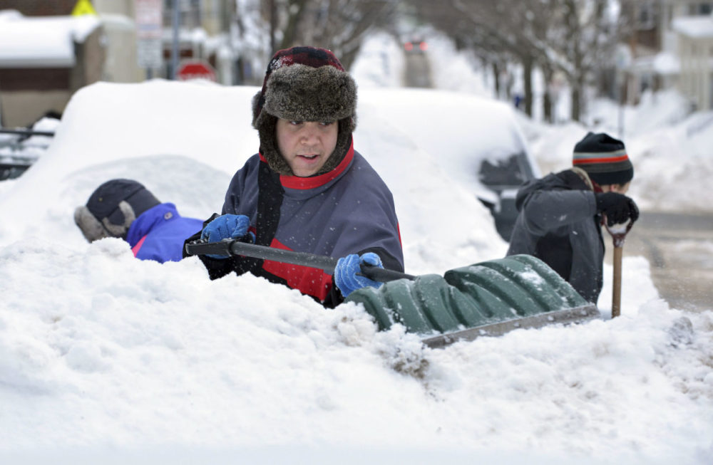 Will Chapman, of Oakland, Calif., digs out his car from between snow piles near the house he was visiting in Somerville, Mass., Tuesday. The latest snowstorm left the Boston area with another two feet of snow, and while many businesses closed for the weather, stores selling winter equipment are staying open for a steady influx of customers. (Josh Reynolds/AP)