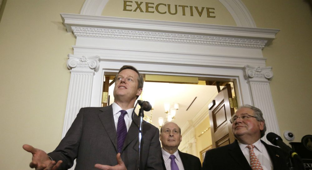 Republican Gov. Charlie Baker, left, speaks to reporters as Democratic legislative leaders Senate President Stanley Rosenberg, center, and House Speaker Robert DeLeo look on during a news conference Jan. 12, outside the governor's office at the State House in Boston. (Steven Senne/AP)