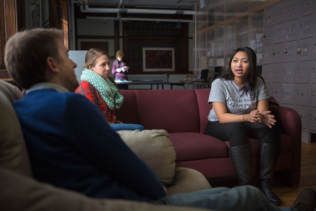 """At Lowell's United Teen Equality Center, Ginny Chhuon, 21, right, talks with Elizabeth Porrazzo, a transitional coach, and Geoff Foster, director of organizing and policymaking. """"I think I probably would be homeless if I didn't find this place,"""" Chhuon says of UTEC. (Jesse Costa/WBUR)"""