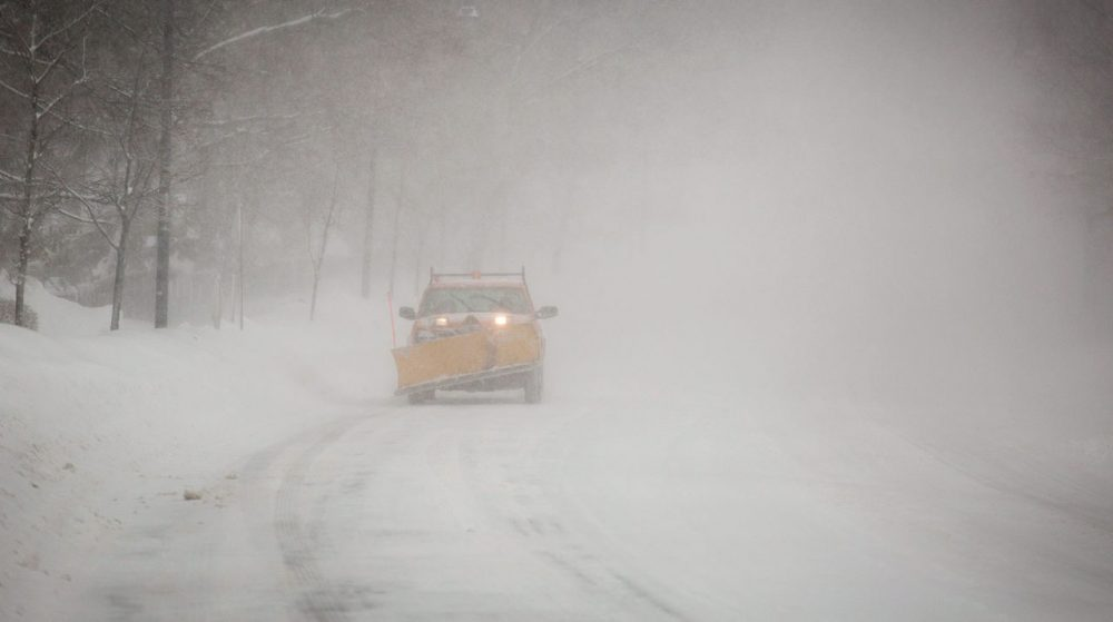 A snow plow drives on Fresh Pond Parkway in Cambridge Sunday morning. (Robin Lubbock/WBUR)