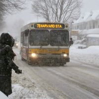 J. Kates: When public transportation grinds to a halt, we throw our iciest snowballs at the people working to get and keep the trains and buses moving. In this photo, Alma Az, 43, waits for a bus on Concord Ave. Cambridge, as she makes her way to work in Copley Square, Mon., Feb. 9, 2015. (Robin Lubbock/WBUR)
