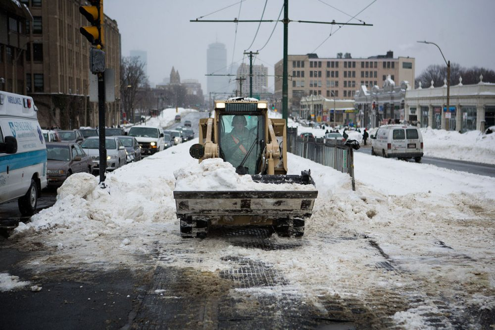 The Massachusetts National Guard 379th Engineering Company clears snow from the Green Line at the intersection of Commonwealth Avenue and St. Paul Street in Boston on Tuesday afternoon. (Jesse Costa/WBUR)