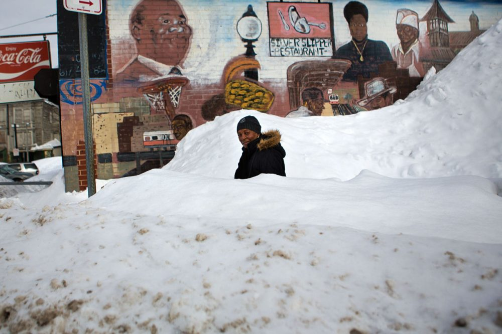 Pauline Sheridan, 82, navigates a small winding path through a large snow bank in front of the Silver Slipper Restaurant at the intersection of Washington St and Malcolm X Blvd. Many people in Dudley Sq. complain the roads and sidewalks around Roxbury have not been cleared properly. (Jesse Costa/WBUR)