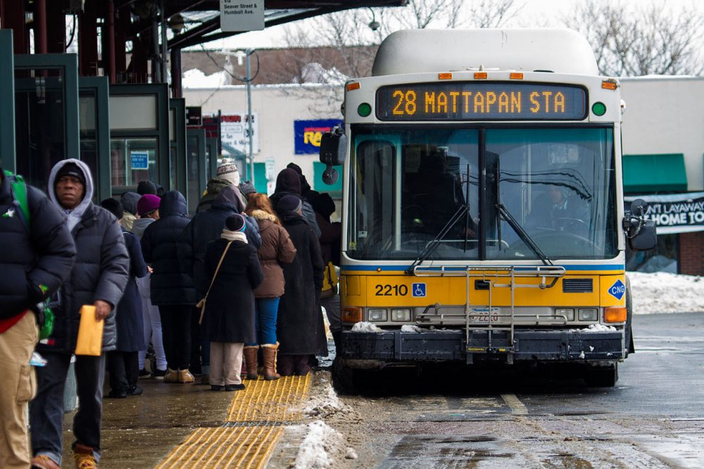 As the MBTA considers  two fare hike proposals, many opponents say increases to the cost of a monthly bus pass would burden many residents. Pictured: Commuters board the #28 Mattapan Station bus at Dudley Square MBTA station on Feb. 18, 2015. (Jesse Costa/WBUR)