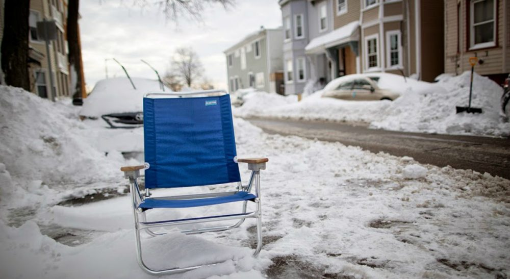 To save, or not to save your shoveled out parking spot? The answer to that question reveals more about us than we may realize. In this photo, a blue beach chair marks a parking space on I St. in South Boston, Jan. 28, 2015. (Robin Lubbock/WBUR)