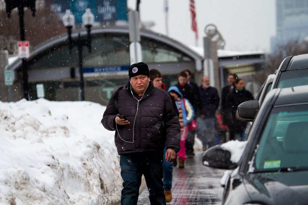 Blocked by snow, commuters walk in the street after leaving Maverick station Thursday. (Jesse Costa/WBUR)