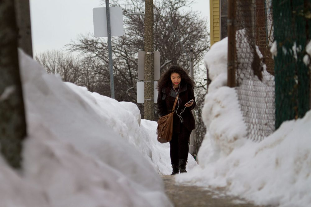 Shaena Sandoval walks through a narrow path on Maverick Street Thursday on her way to school.