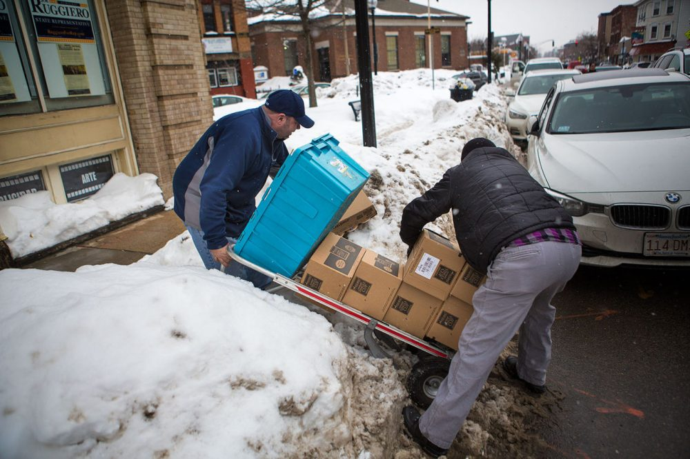 Anthony Dimare, left, loses the items he is delivering in February in East Boston. (Jesse Costa/WBUR)