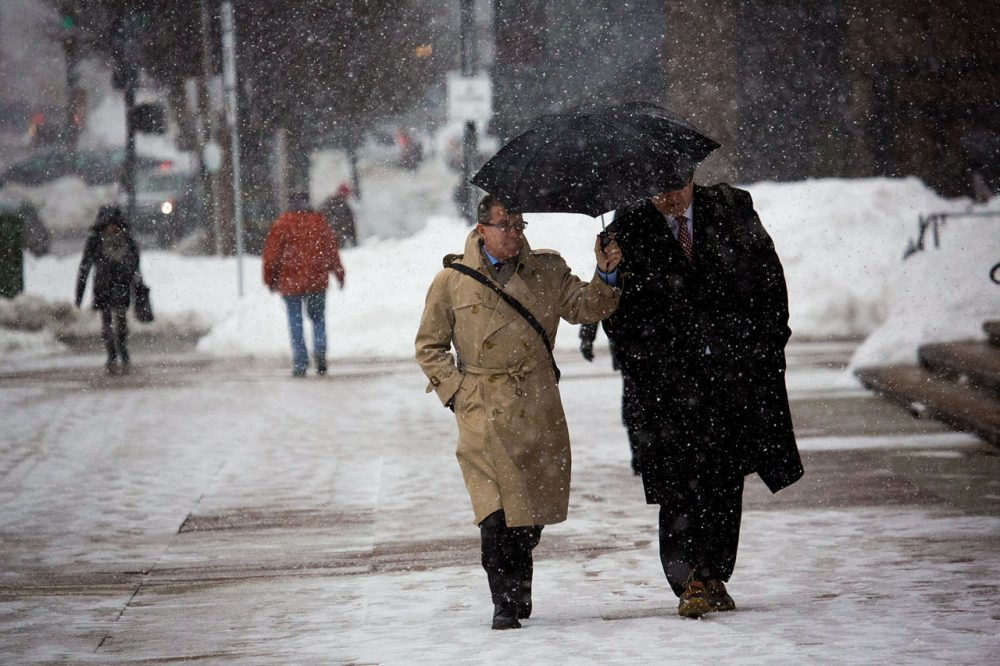 Two businessmen share an umbrella while walking down Dartmouth Street in Copley Square during a snowstorm on Feb. 5. (Jesse Costa/WBUR)