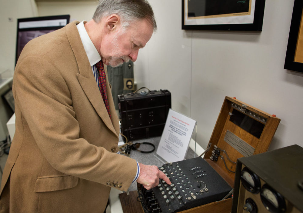 "Museum of World War II founder Kenneth Rendell demonstrates how to encode a message using an Enigma machine. Here, as he presses on the ""T"" on the keyboard, the ""X"" lights up in the panel above. (Robin Lubbock/WBUR)"