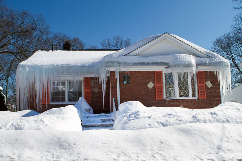 A house on Woodhaven Street in Mattapan with lots of excessive snow and ice on the roof. (Jesse Costa/WBUR)
