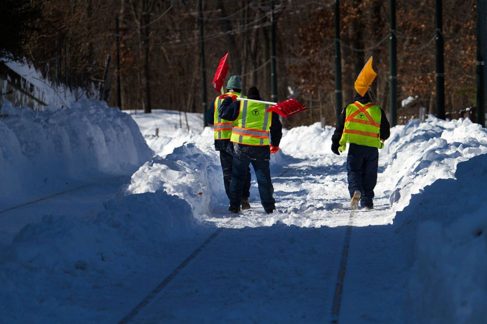 Workers clear snow from the MBTA's Mattapan trolley line on Friday. The line reopened on Monday. (Jesse Costa/WBUR)