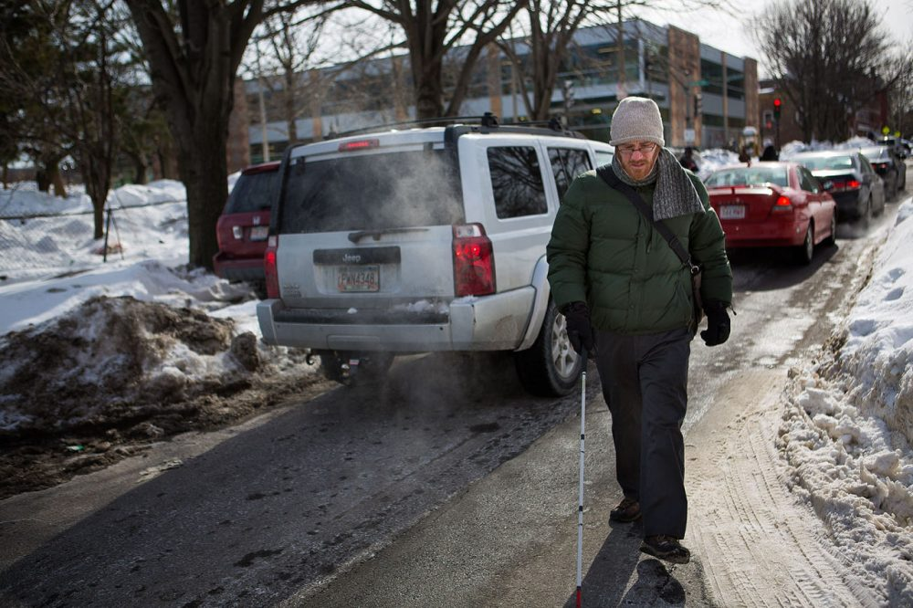 Kyle Robidoux, who's legally blind, walks on Shawmut Avenue Tuesday because the crosswalk curb cuts are not properly cleared and are blocked by snowbanks. (Jesse Costa/WBUR)