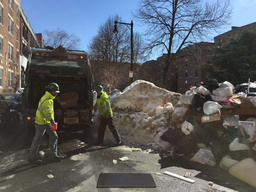Trash collectors work through a giant pile of garbage on Hemenway Street. (Simon Rios)