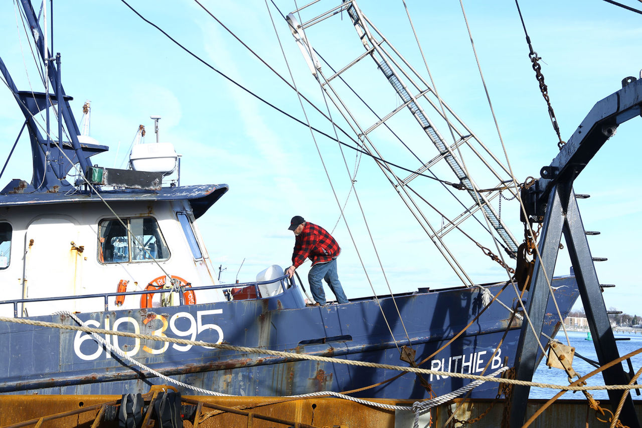 """Willis Blount stands on his boat, """"Ruthie B."""" He's spent more than a half century fishing, and in recent years, he's pressed on through the scary financial realities that have befallen his industry. (Simón Rios/WBUR)"""