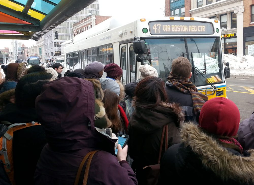 Commuters wait for a MBTA bus in Central Square in Cambridge Thursday. (Zeninjor Enwemeka/WBUR)