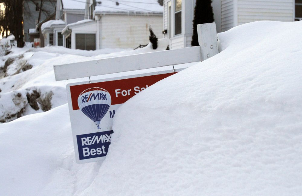A sign advertising a home for sale peaks from a mound of snow in Marlborough Monday. Real estate agents have found that purchase closings are being held up because of the heavy snowfall in the Boston area. (Bill Sikes/AP)