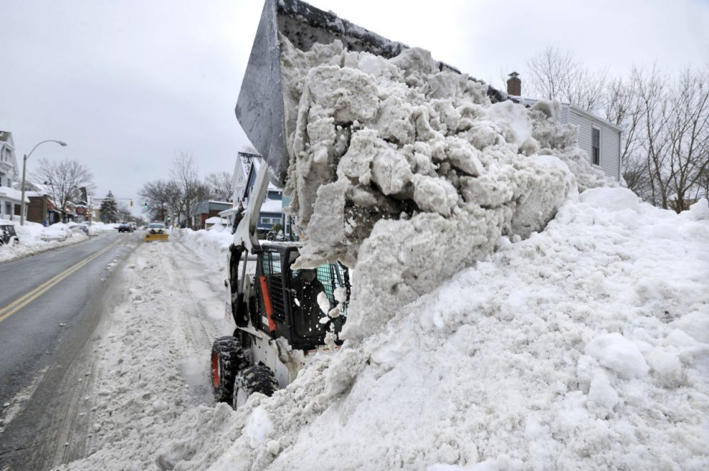 Near Davis Square in Somerville Tuesday, crews worked to remove snow from city streets. (Josh Reynolds/AP)