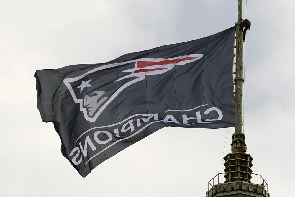 A worker secures a New England Patriots flag atop a building prior to a victory parade in Boston Wednesday to honor the Patriots win over the Seattle Seahawks 28-24 in Super Bowl XLIX Sunday. (Steven Senne/AP)