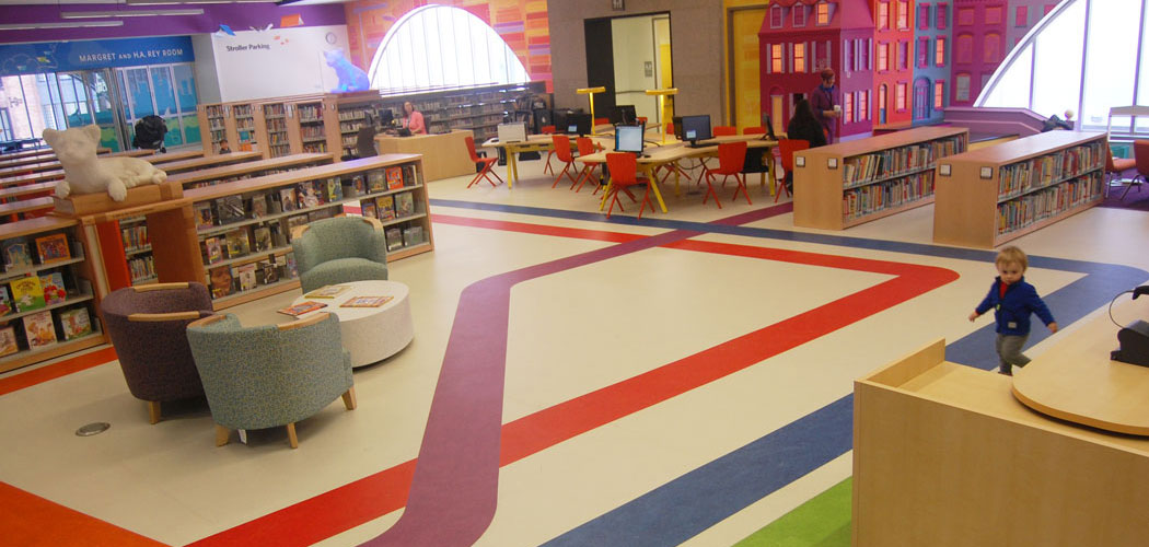 """We want people to know they're in the library, of course, but also to know they're in Boston,"" Colford says. Part of the way this makes its way into the Children's Library is colored stripes running along the floor that echo MBTA train maps. (Greg Cook)"