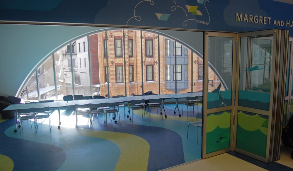 "The Children's Library ""has a retractable glass wall that has a Curious George theme,"" Colford says. ""There's a screen and projector and curtain for theatrical performances. There is small bleacher seating for kids. There's a sink and wet room for crafts."" (Greg Cook)"