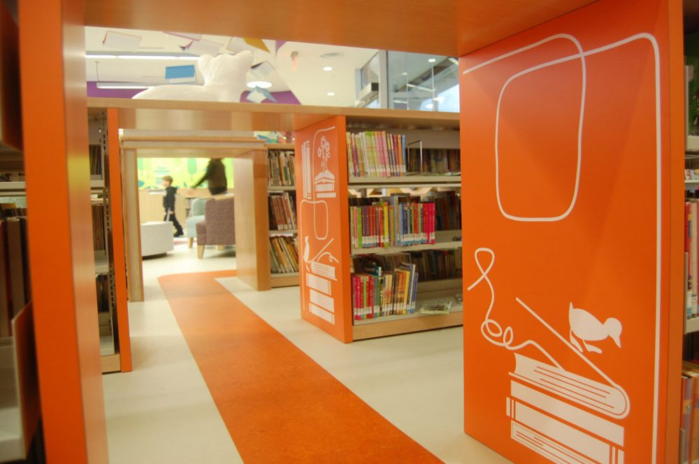 Gaps between shelves in the Children's Library become tunnels to explore. (Greg Cook)