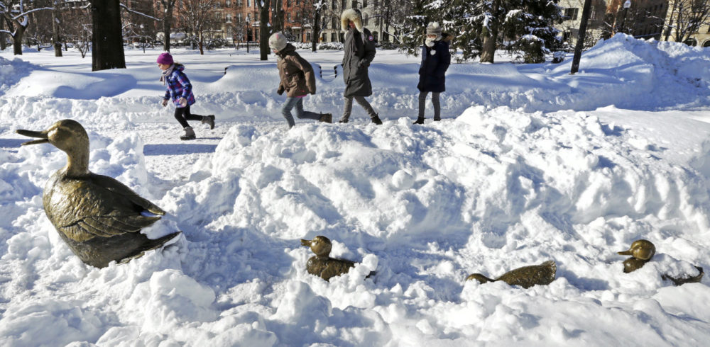 """Children run through the Boston Public Garden, passing the nearly snow-covered """"Make Way for Ducklings"""" statues, after the last major snowstorm. The city is bracing for another couple feet of snow. (Charles Krupa/AP)"""