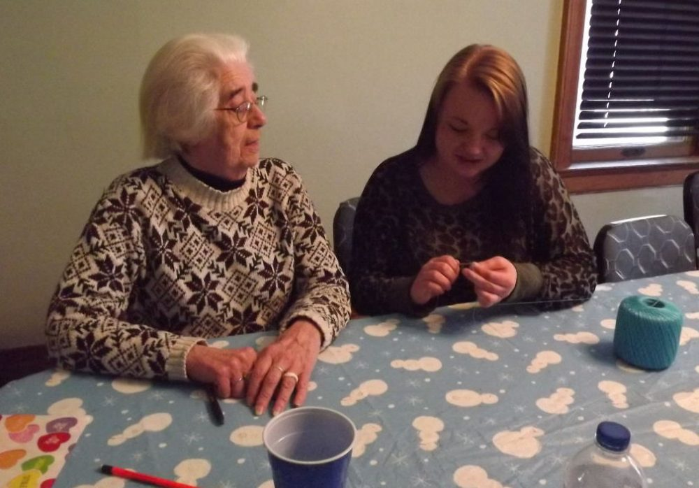 Sister Sue Kintzele crochets with a Dismas House Resident. (Courtesy Maria Kaczmarek)