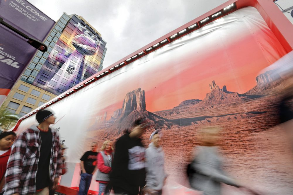 Pedestrians walk past a mural of an Arizona landscape as a banner of the Vince Lombardi Super Bowl Trophy decorates a building in Phoenix. The New England Patriots face the Seattle Seahawks in Super Bowl XLIX today, in Glendale, Ariz. (David Goldman/AP)