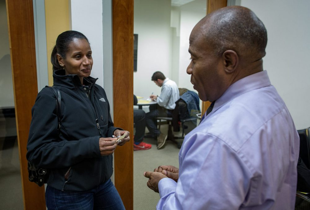 Pamela Monteiro, of Dorchester, talks with Alan Gentle, program director of the Roxbury Center for Financial Empowerment, in Dudley Square. Monteiro wants to start her own catering business. (Robin Lubbock/WBUR)