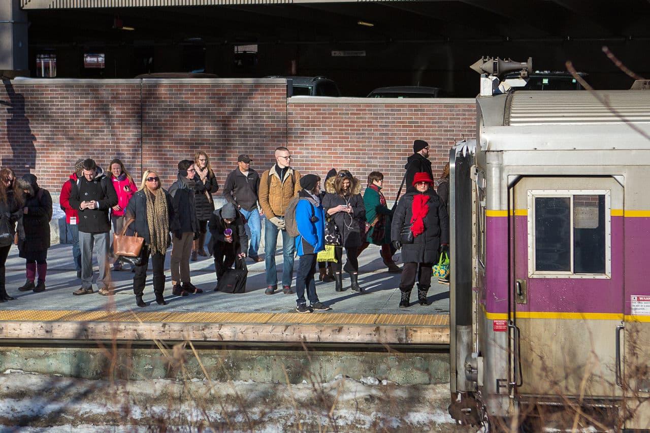 Commuters wait on the platform in Salem as an MBTA commuter rail train arrives in early March. (Jesse Costa/WBUR)