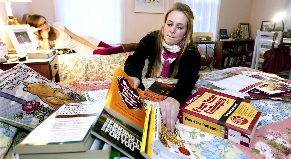 In this photo, Kim Pollock, 17, facing center, goes through college materials, as her sister Lindsay, 15, back left, watches, in her bedroom in Bedford, N.H., Thursday, Nov. 11, 2010. (Cheryl Senter/AP)