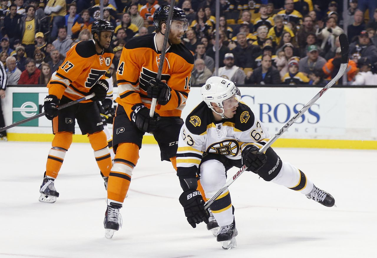 Boston Bruins' Brad Marchand (63) watches his game-winning goal in front of Philadelphia Flyers' Sean Couturier (14) and Wayne Simmonds (17). (Michael Dwyer/AP)