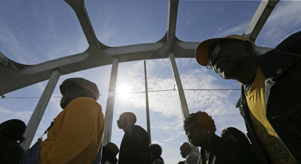 In this photo, crowds of people walk toward Selma after taking a symbolic walk across the Edmund Pettus Bridge, Sunday, March 8, 2015, in Selma, Ala. (Gerald Herbert/AP)