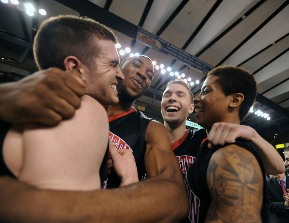 Northeastern celebrates after topping William & Mary Monday night in the CAA tournament championship game. The Huskies are in the Big Dance for the first time since 1991. (Caleb Donnelly/AP)