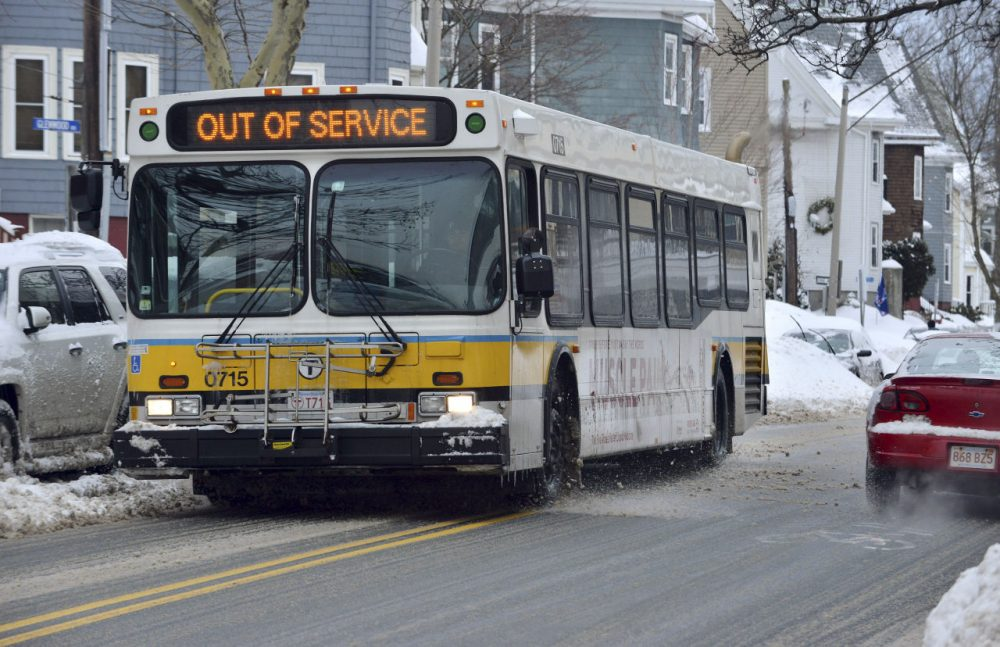 An out-of-service MBTA bus rolls through Somerville after several snowstorms in February. (Josh Reynolds/AP)