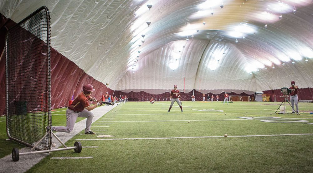 This winter's record-breaking snowfall has some college sports teams wondering where they will be playing their first spring games, including Boston College's baseball team, pictured here during a practice earlier this week. (Jesse Costa/WBUR)