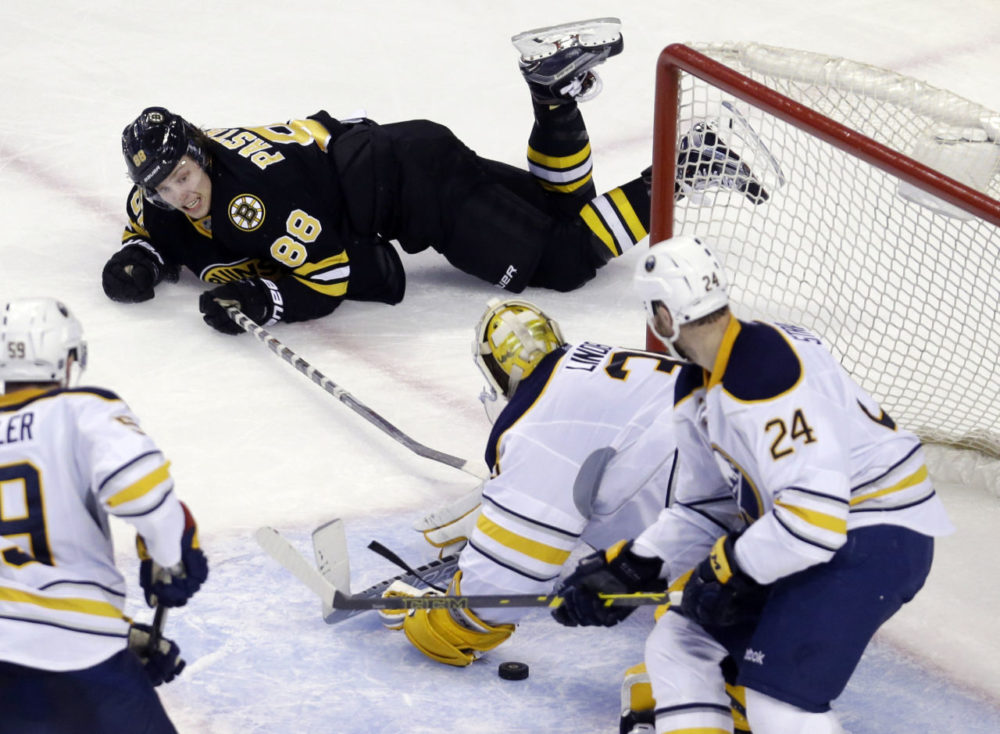 Boston Bruins right wing David Pastrnak (88) tries to reach in for the puck but Buffalo Sabres goalie Anders Lindback (35) is there to keep him from scoring as Buffalo Sabres defenseman Tyson Strachan (24) looks on during the third period of an NHL hockey game in Boston, Tuesday. (Elise Amendola/AP)