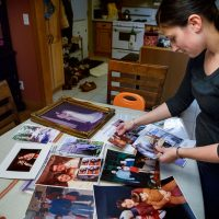 Valerie Alfeo files through a table full of family photos at her home in Waltham. Her father, Ted Washburn, took his own life in 2011. He was 54.  (Jesse Costa/WBUR)