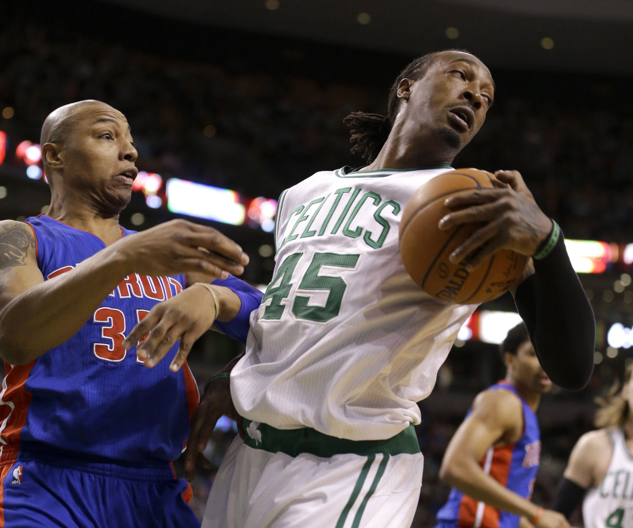 Detroit Pistons forward Caron Butler (31), and Boston Celtics forward Gerald Wallace (45), grapple over a loose ball in the second quarter Sunday's game. (Steven Senne/AP)