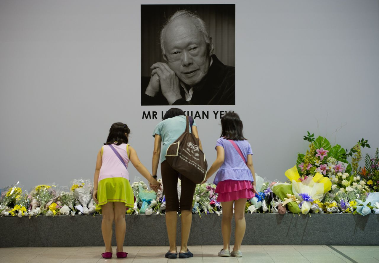 Singaporeans pray in front of an image of late former prime minister Lee Kuan Yew alongside messages and flowers left at the Tanjong Pagar community center following Lee's death in Singapore on March 23, 2015. (Mohd Rasfan/AFP/Getty Images)