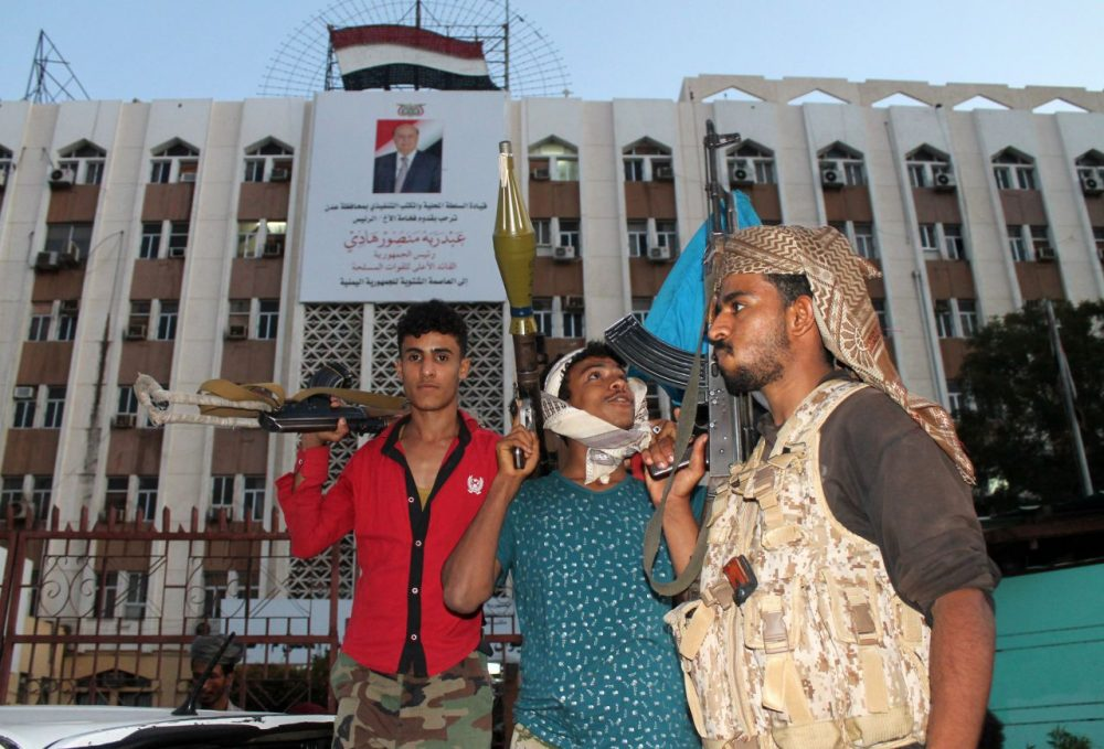 Heavily armed Yemeni fighters loyal to Yemeni President Abedrabbo Mansour Hadi (portrait on the poster) stand guard in front of the governorate building on March 18, 2015, in the southern city of Aden. Security in Aden resembles a time-bomb as forces loyal to Hadi, and others opposing him, share control over the southern city that shelters the embattled leader.  (AFP/Getty Images)
