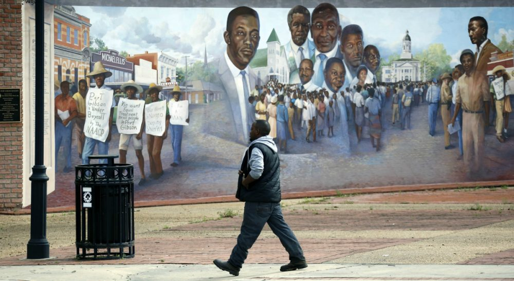 A Port Gibson, Miss., resident walks past a mural depicting a successful economic boycott protest in the 1960's, Monday, March 23, 2015. A small group of residents and friends gathered nearby to show support for the Otis Byrd's family and to call on federal and state authorities to do a thorough investigation into his death. Byrd's body was found last Thursday, hanging from a sheet from a tree in a rural area outside of Port Gibson. The FBI is consulting with its behavioral analysis unit as it continues investigating the hanging death of Byrd. (Rogelio V. Solis/AP)