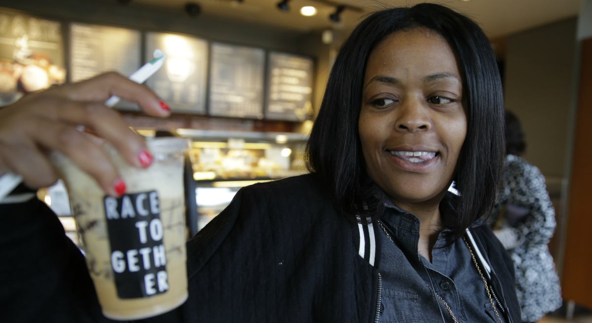 """Wendy Kaminer:  Important conversations often occur naturally in public spaces like Starbucks, but they are rarely about important subjects. In this March 18, 2015 file photo, Larenda Myres holds an iced coffee drink with a """"Race Together"""" sticker on it at a Starbucks store in Seattle. Starbucks baristas will no longer write """"Race Together"""" on customers' cups starting Sunday, ending as planned a visible component of the company's diversity and racial inequality campaign that had sparked widespread criticism in the week since it took effect. (Ted S. Warren/AP)"""