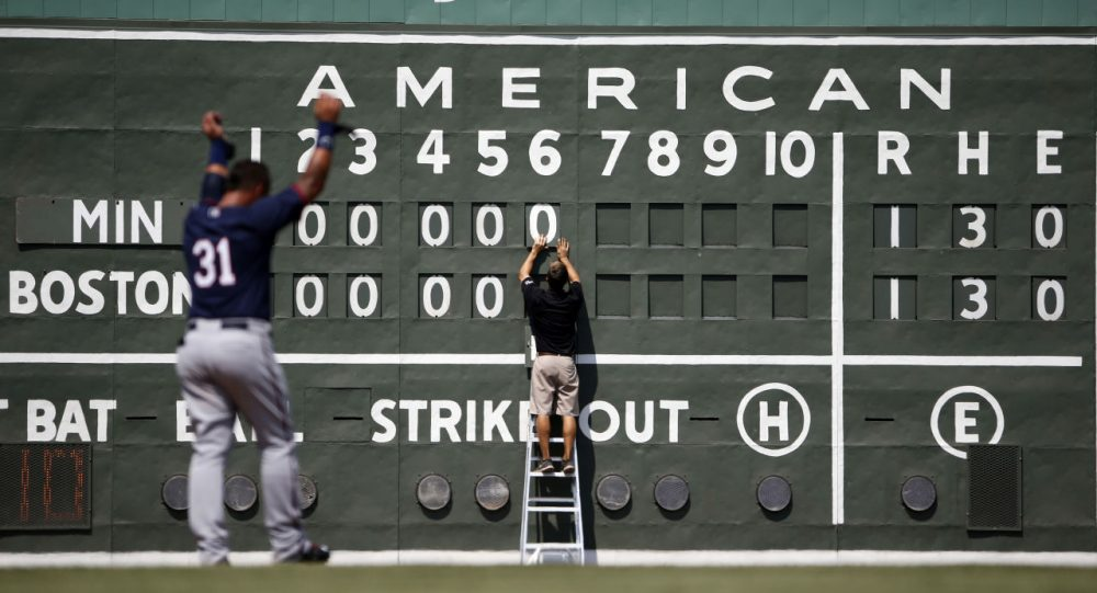 This scoreboard likely looks familiar to Boston Red Sox fans. Down at the team's spring training facility, Sox intern Tim Batesole changes the scoreboard during a game on March 18 in Fort Myers, Fla. (Brynn Anderson/AP)