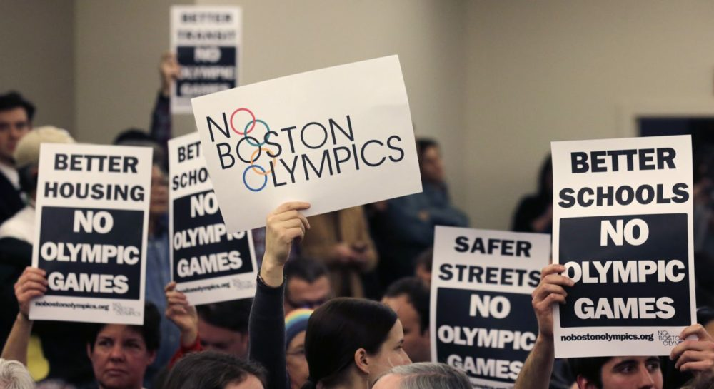 People hold up placards against bringing the Olympic Games to Boston during the first public forum regarding the city's 2024 Olympic bid in February, 2015. (Charles Krupa/AP)