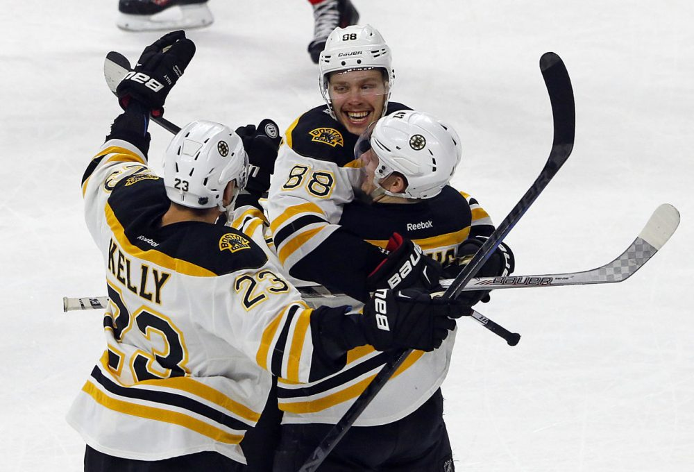 Boston's David Pastrnak (88) celebrates his game-winning overtime goal with teammates Torey Krug (47), and Chris Kelly (23). (Karl B DeBlaker/AP)