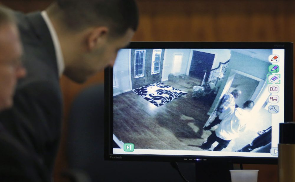 Former New England Patriots football player Aaron Hernandez, center, looks on as a still frame from surveillance video is displayed on a monitor during his murder trial Thursday. (Steven Senne/AP/Pool)