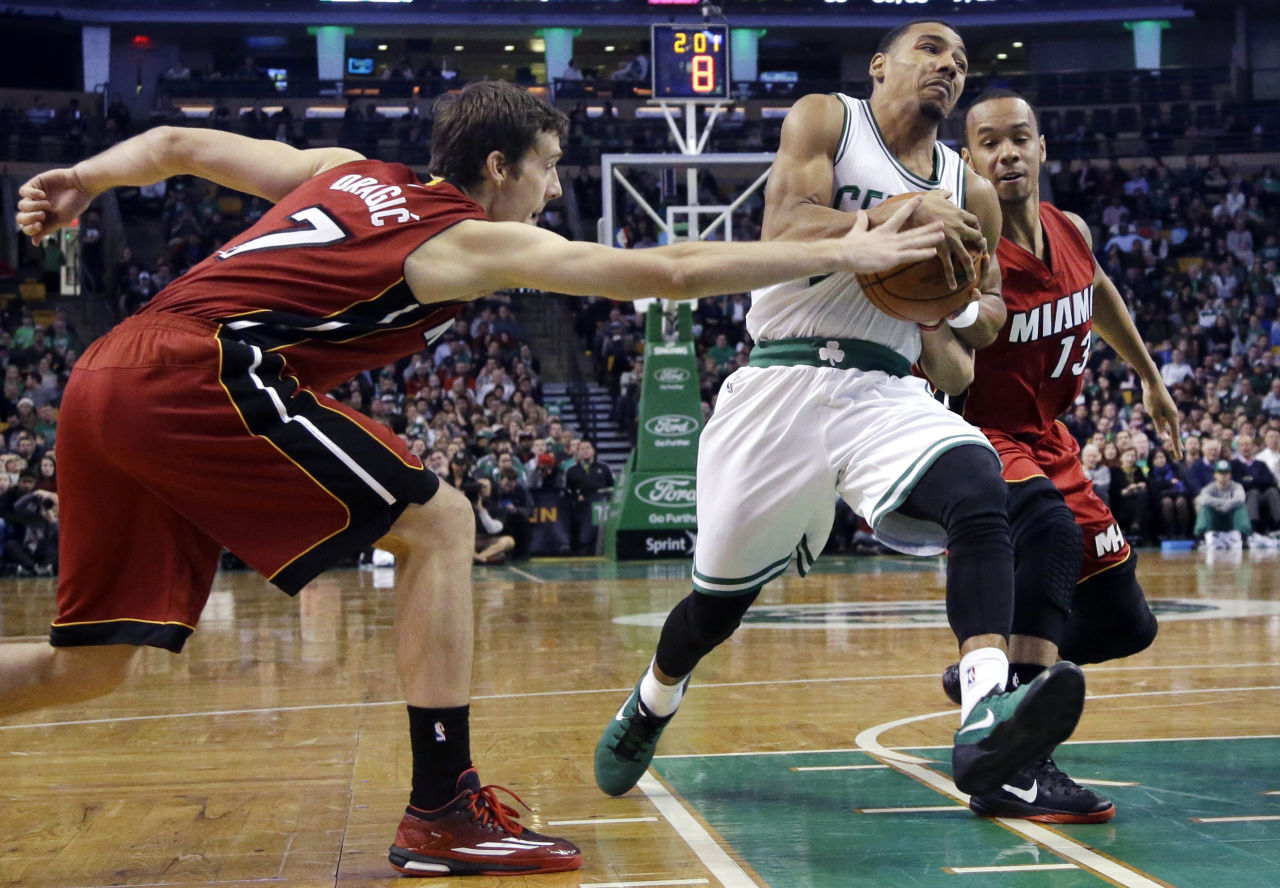 Celtics guard Phil Pressey splits the defense of Miami Heat guards Goran Dragic (7) and Shabazz Napier (13) as he drives to the hoop in the second half. (AP/Elise Amendola)