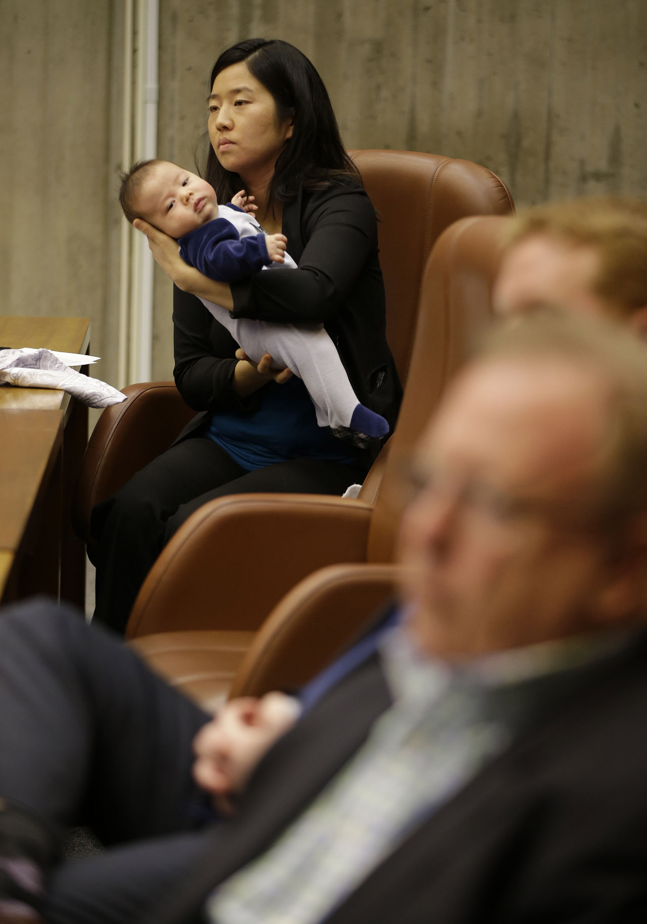 Boston City Councilwoman Michelle Wu holds her eleven week-old son Blaise Pawarski as members of Boston 2024 answer questions during the first meeting of the Boston City Council on the city's bid to be awarded the 2024 Summer Olympics, Friday March 6, 2015, at City Hall in Boston.  (AP)